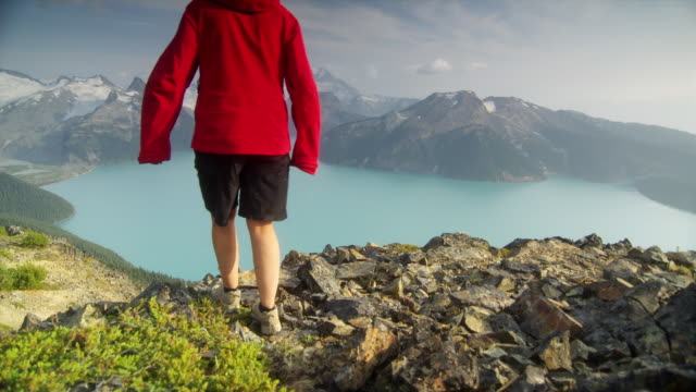 ws pan ha two female hikers sitting down on edge of cliff overlooking lake surrounded by snow capped mountains, garibaldi provincial park, squamish, british columbia, canada - garibaldi park stock videos & royalty-free footage