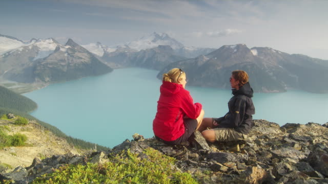 WS PAN HA Two female hikers sitting down on edge of cliff overlooking lake surrounded by snow capped mountains, Garibaldi Provincial Park, Squamish, British Columbia, Canada