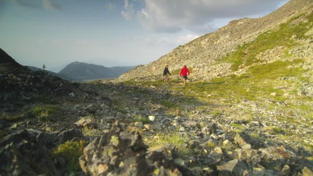 ws r/f pan two female hikers walking through mountain landscape, garibaldi provincial park, squamish, british columbia, canada - garibaldi park stock videos & royalty-free footage