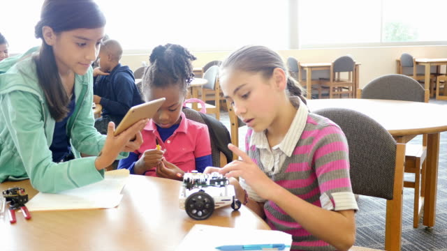 Two female Hispanic elementary school students work with younger African American female student on a robot at STEM school