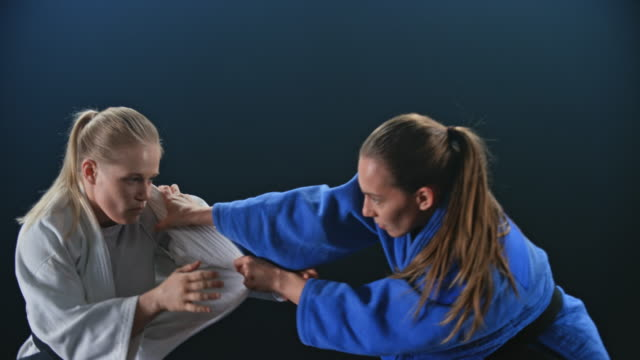 slo mo two female judoists trying to get a grab of the opponent in a fight - world sports championship stock videos & royalty-free footage