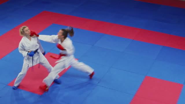 vídeos de stock, filmes e b-roll de dois karaté fêmeas em uma competição de luta - karate