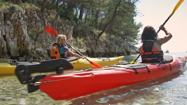 Two female kayakers paddling out of the sunny bay in their sea kayaks