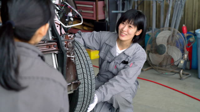 two female mechanics working together in a car garage - jumpsuit stock videos & royalty-free footage