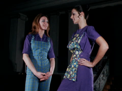 Two female models pose on catwalk One is wearing green dungaress the other is wearing a purple dress with a floral front panel 1970