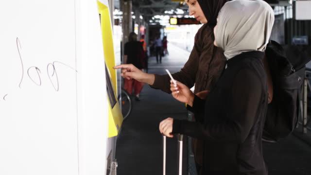 zwei muslimischen freundinnen öpnv-ticket (zeitlupe) kaufen - fahrkarte oder eintrittskarte stock-videos und b-roll-filmmaterial