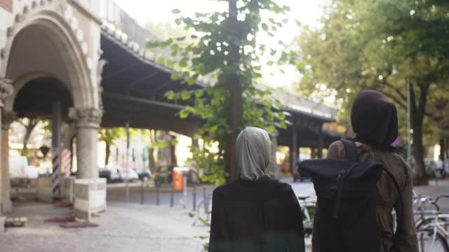 two female muslim friends commuting in berlin (slow motion) - turismo urbano video stock e b–roll