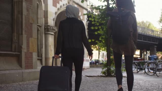 vídeos de stock, filmes e b-roll de dois amigos muçulmanos femininos pendulares em berlim (câmera lenta) - vestuário modesto