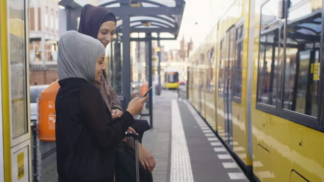 two female muslim friends looking at transport timetable on smart phone (slow motion) - real people stock videos & royalty-free footage