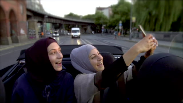 Two female muslim friends riding in convertible car and taking selfies