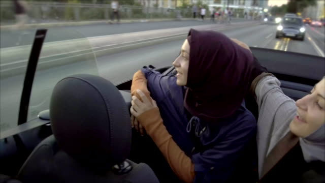 Two female muslim friends riding in convertible car through Berlin
