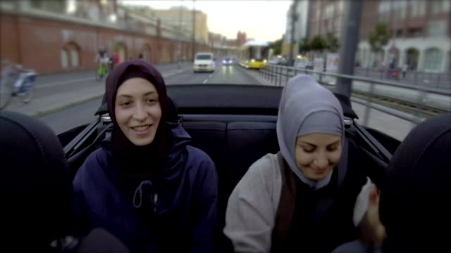 vídeos de stock e filmes b-roll de two female muslim friends riding in convertible car through berlin - lenço na cabeça enfeites para a cabeça