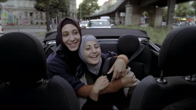 zwei muslimischen freundinnen reiten im cabrio durch berlin - islam stock-videos und b-roll-filmmaterial