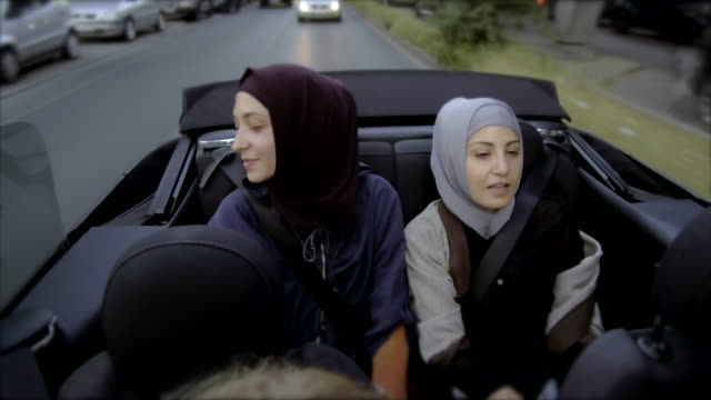 two female muslim friends riding in convertible car through berlin - hijab stock videos and b-roll footage
