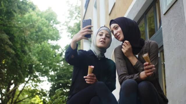 vídeos de stock, filmes e b-roll de dois amigos muçulmanos femininos tomando um selfie (câmera lenta) - vestuário modesto