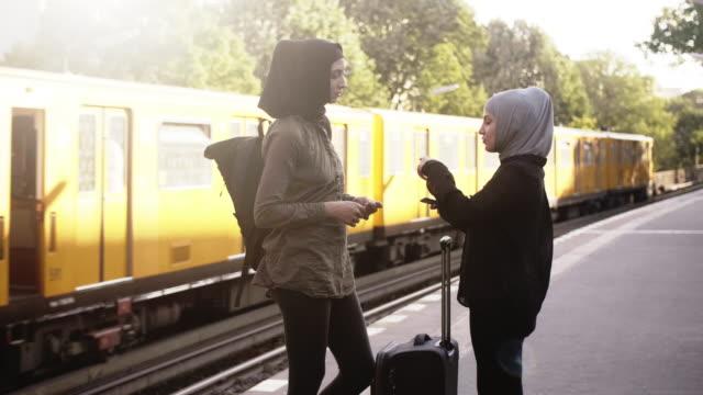 stockvideo's en b-roll-footage met twee vrouwelijke islamitische vrienden praten op het metrostation (slow motion) - stadsreis