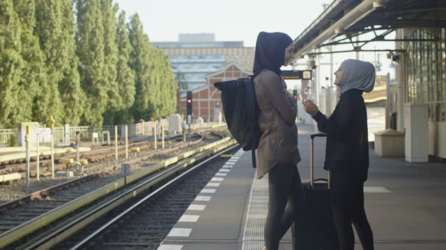 two female muslim friends waiting for metro in berlin (slow motion) - real people stock videos & royalty-free footage
