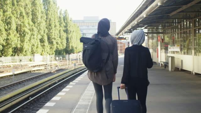 vídeos de stock, filmes e b-roll de dois amigos muçulmanos femininos esperando por metro de berlim (câmera lenta) - vestuário modesto