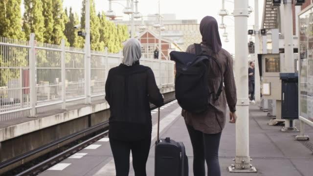 vídeos de stock, filmes e b-roll de dois viajantes muçulmanos femininos andando na estação de metro (câmera lenta) - vestuário modesto