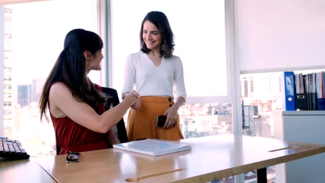 two female office coworker reach an agreement and shake hands 4k video - employee engagement stock videos & royalty-free footage