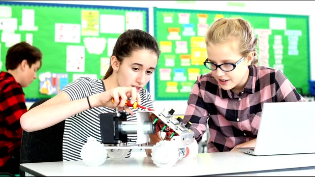Two Female Pupils Building Robotic Car In Science Lesson