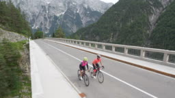 AERIAL Two female road cyclists riding on a bridge across a gorge in the mountains