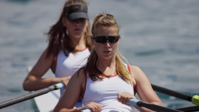 two female rowers sculling on a sunny lake - rowing stock videos & royalty-free footage