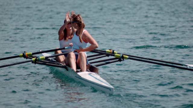 slo mo two female rowing athletes doing a high five on a double scull - rowing stock videos & royalty-free footage