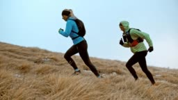SLO MO Two female runner running up a grassy slope on a cold day