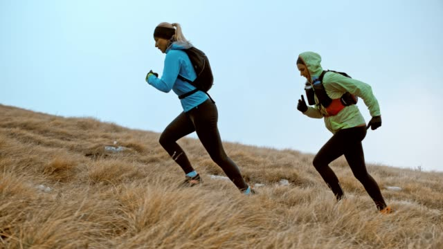 slo mo two female runner running up a grassy slope on a cold day - mature women stock videos & royalty-free footage