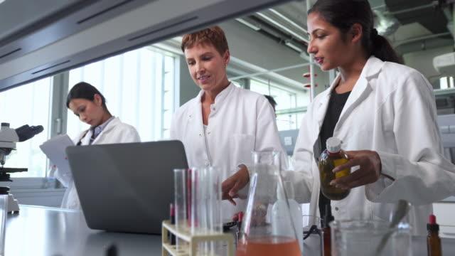 två kvinnliga forskare talar om sina experiment i laboratoriet - biokemi bildbanksvideor och videomaterial från bakom kulisserna