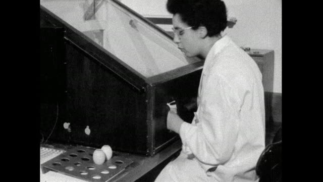 vídeos de stock e filmes b-roll de two female scientists test flu samples in lab; 1959 - 1950 1959