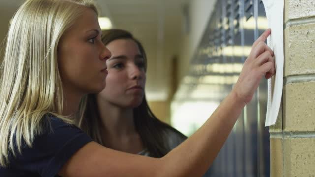 stockvideo's en b-roll-footage met ms two female students (16-17) reading list in corridor / spanish fork city, utah, usa - testuitslag
