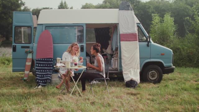 two female surfers eating breakfast in front of van - furgone video stock e b–roll