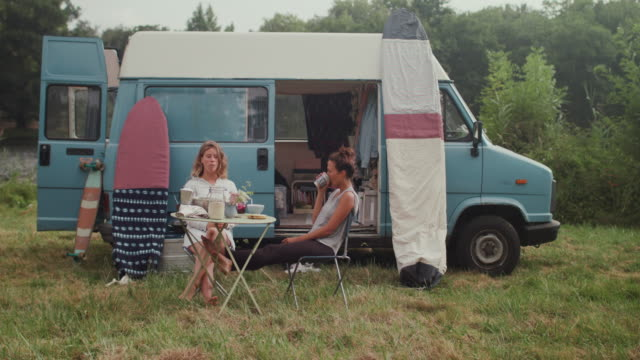 Two female surfers eating breakfast in front of van