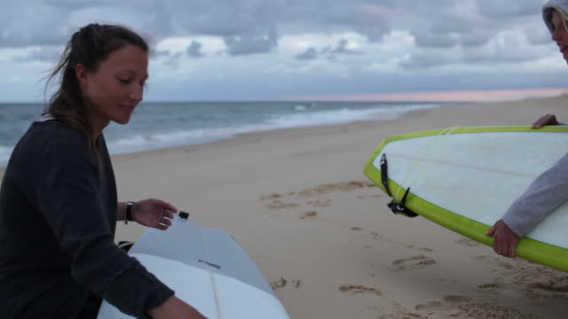 two female surfers getting ready and waxing boards for surf at beach in southern france. - giving stock videos & royalty-free footage
