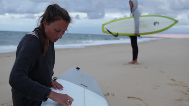 Two female surfers getting ready and waxing boards for surf at beach in southern France.