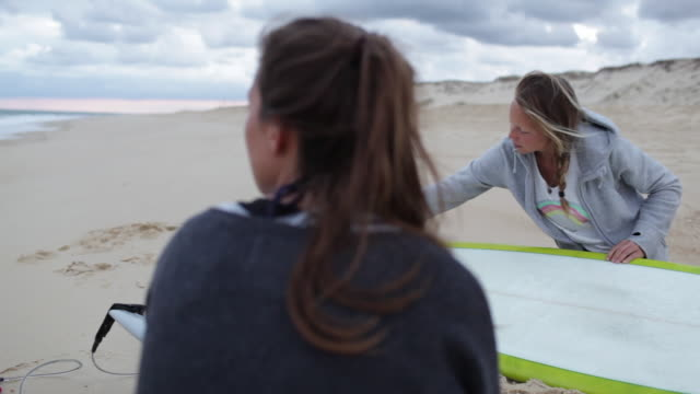 two female surfers getting ready and waxing boards for surf at beach in southern france. - ponytail stock videos & royalty-free footage