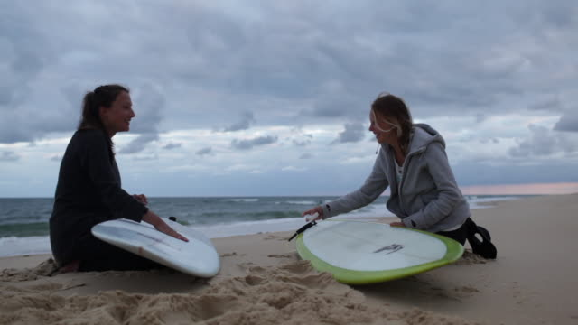 two female surfers getting ready and waxing boards for surf at beach in southern france. - coda di cavallo video stock e b–roll