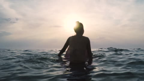 two female surfers in bikinis sitting/paddling on surfboards in the ocean at sunset in southern france - europäischer abstammung stock-videos und b-roll-filmmaterial