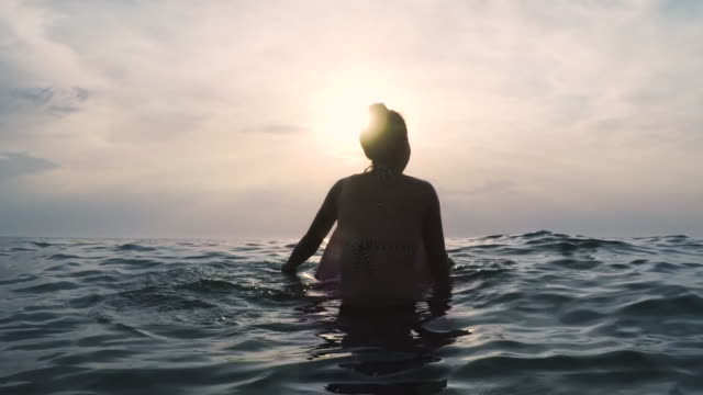 two female surfers in bikinis sitting/paddling on surfboards in the ocean at sunset in southern france - stillhet bildbanksvideor och videomaterial från bakom kulisserna