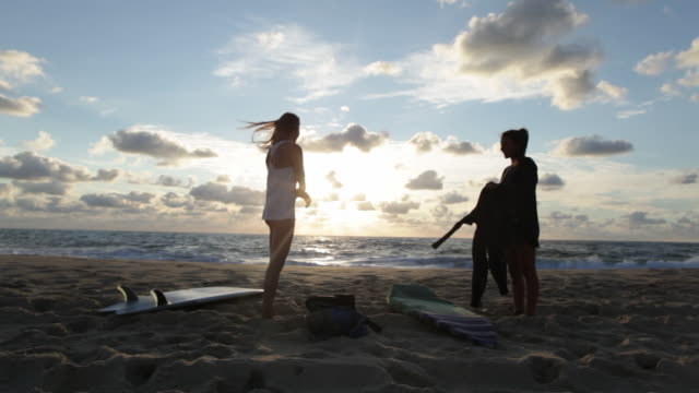 Two female surfers putting on wetsuits, getting ready for evening surf at the beach in Southern France