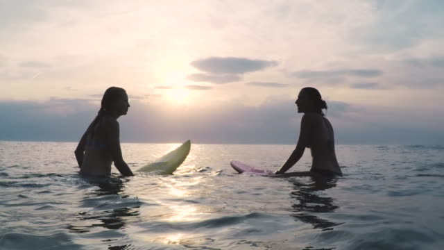 Two female surfers sitting on surfboards in bikinis in the ocean at sunset in Southern France
