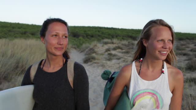 two female surfers standing on sand dune looking out in southern france - nose piercing stock videos & royalty-free footage