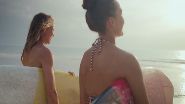 Two female surfers walking toward water, looking at surf on beach with surfboards in bikinis at Atlantic coast in South of France.
