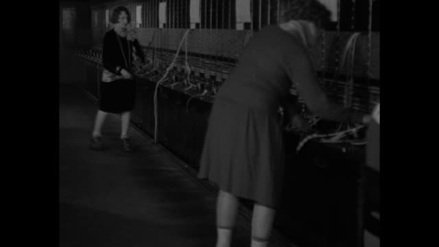 two female switchboard operators on roller skates working / note exact day not known - 電話交換機点の映像素材/bロール