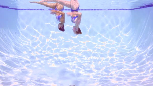 MS Two female synchronized swimmers underwater while performing routine underwater view