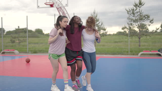 two female teammates helping injured african woman on basketball court - injured stock videos & royalty-free footage