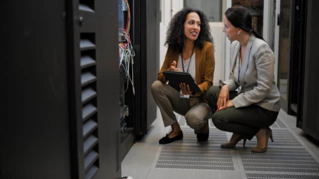 ld two female technicians squatting in the server room discussing connections - tecnico video stock e b–roll