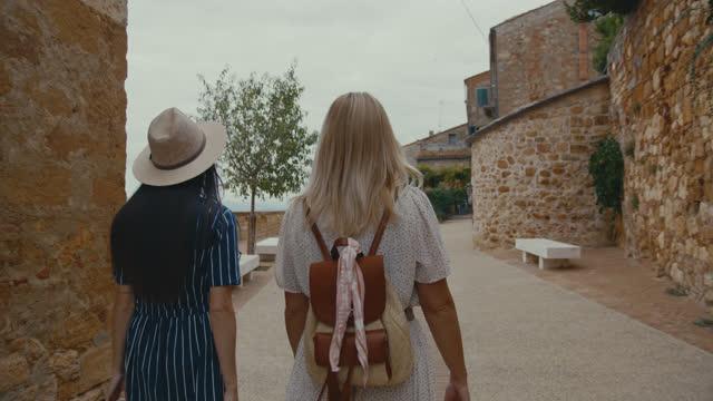 vídeos de stock e filmes b-roll de slo mo two female tourists walking through an alley in the town pienza - cidade pequena